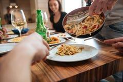 Équipez faire cuire des pâtes et dîner avec des amis à la table Photographie stock