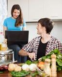 Équipez faire cuire la nourriture tandis qu'amie regardant l'ordinateur portable Image libre de droits