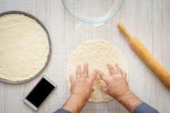Équipez faire cuire la pâte pour deux pizzas sur la table en bois photos libres de droits
