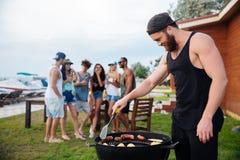 Équipez faire cuire les sauseges et les légumes grillés sur la partie de barbecue Image stock