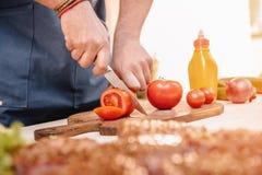 Équipez faire des hamburgers et couper les tomates rouges dehors Photographie stock