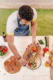 Équipez faire des hamburgers et couper les tomates rouges dehors Photos stock