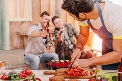 Équipez faire des hamburgers tandis que ses amis buvant de la bière se reposant derrière Image stock