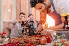 Équipez faire des hamburgers tandis que ses amis buvant de la bière se reposant derrière Photographie stock