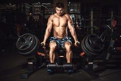 Équipez faire l'exercice pour des muscles de triceps dans la machine d'ascenseur dans le gymnase images stock