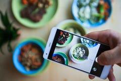 Équipez faire la photo de son déjeuner sur le smartphone Image stock