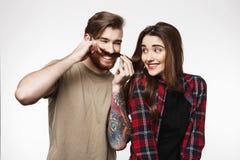 Équipez faire les visages drôles jouant avec des cheveux du ` s de fille sur le blanc Photographie stock libre de droits