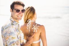 Équipez faire un symbole du soleil sur le dos de la femme tout en appliquant une lotion de protection solaire Photo libre de droits