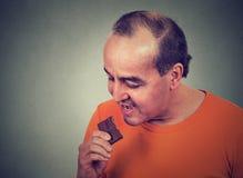 Équipez fatigué des restrictions de régime implorant le chocolat de bonbons Images libres de droits