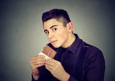 Équipez fatigué des restrictions de régime implorant le chocolat de bonbons Photo stock