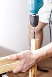 Équipez forer un trou électrique forent dedans une planche en bois à sa maison Photo stock