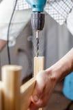 Équipez forer un trou électrique forent dedans une planche en bois à sa maison Image stock