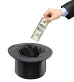 Équipez insérer un dollar dans un chapeau noir Photographie stock