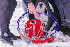 Équipez installer des chaînes de neige sur les roues de la voiture photographie stock libre de droits
