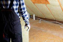 Équipez installer la couche thermique d'isolation de toit - utilisant le minerai courtisez photographie stock