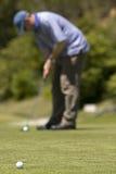 Équipez jouer au golf sur un terrain de golf vert frais Photo libre de droits