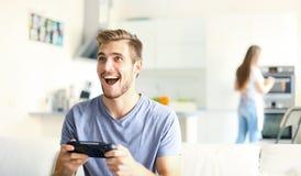 Équipez jouer des jeux vidéo tandis que son amie faisant cuire dans la cuisine Images libres de droits