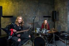 Équipez jouer la guitare électrique et la femme s'asseyant aux tambours réglés dans le studio musical Photos libres de droits