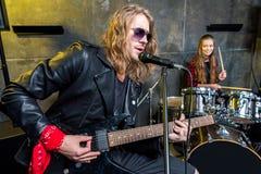 Équipez jouer la guitare électrique et la femme s'asseyant aux tambours réglés dans le studio musical Photo libre de droits