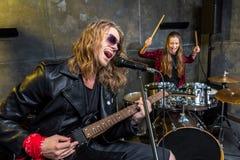 Équipez jouer la guitare électrique et la femme s'asseyant aux tambours réglés dans le studio musical Photographie stock