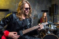 Équipez jouer la guitare électrique et la femme s'asseyant aux tambours réglés dans le studio musical Photo stock