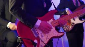 Équipez jouer la guitare électrique sur une étape, vue musicale de plan rapproché de concert banque de vidéos