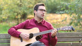 Équipez jouer la guitare acoustique et le chant en parc banque de vidéos