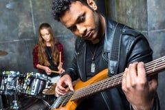 Équipez jouer la guitare avec la femme jouant des tambours derrière, concept de joueur de guitare électrique Photos libres de droits
