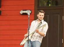 Équipez jouer la guitare et le sourire pendant un concert extérieur Image stock