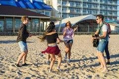 Équipez jouer la guitare et ses amis dansant ensemble Images libres de droits