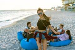Équipez jouer la guitare et ses amis dansant sur la plage de thr Photographie stock