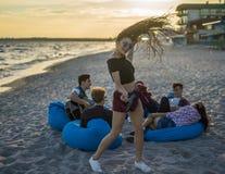 Équipez jouer la guitare et ses amis dansant sur la plage de thr Image libre de droits