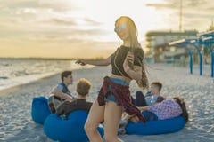 Équipez jouer la guitare et ses amis dansant sur la plage de thr Images libres de droits