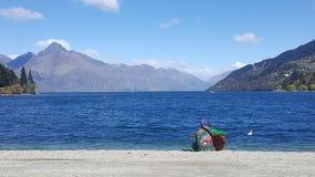 Équipez jouer la guitare par le lac queenstown, Nouvelle-Zélande photos stock