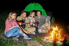 Équipez jouer la guitare pour des amis près du feu la nuit Saison de camping Photos libres de droits
