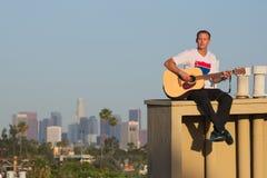 Équipez jouer la guitare sur le toit avec l'horizon de LA Images libres de droits