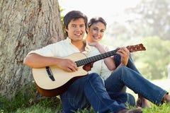 Équipez jouer la guitare tandis qu'en avant avec son ami Photo stock