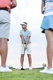 Équipez jouer le golf contre le ciel avec des amis se tenant dans le premier plan Photos stock
