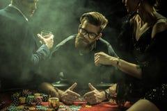 Équipez jouer le tisonnier tandis que des amis s'asseyant sur la table dans le casino Image stock