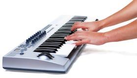 Équipez jouer sur un synthétiseur sur un fond blanc Photos libres de droits