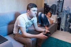 Équipez jouer un jeu vidéo avec son amie qui se trouvant sur ainsi Photographie stock libre de droits