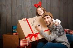 Équipez l'écriture sur le Joyeux Noël de boîte-cadeau se reposant avec l'amie Photo stock