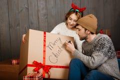 Équipez l'écriture sur le Joyeux Noël de boîte-cadeau se reposant avec l'amie Image libre de droits