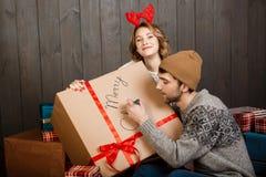 Équipez l'écriture sur le Joyeux Noël de boîte-cadeau se reposant avec l'amie Images libres de droits