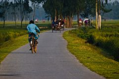 Équipez l'équitation sur une bicyclette dans une photo unique d'isolement par route de village Image stock