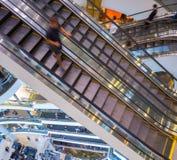 Équipez l'étape de précipitation de personnes de type dans le mouvement sur l'escalator dans le bâtiment de mail Image stock