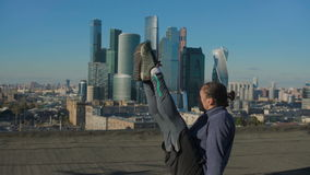 Équipez l'étirage sur le toit contre le contexte de la ville banque de vidéos