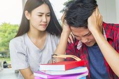 Équipez l'étudiant triste vérifiant un examen échoué se reposant ensemble à la table Image stock