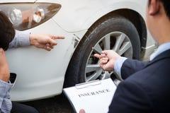 Équipez l'agent voiture près endommagée et de examen de Filling Insurance Form, Image stock
