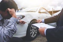 Équipez l'agent voiture près endommagée et de examen de Filling Insurance Form, Images stock